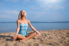 Blondes langhaariges Mädchen in einer blauen Klage ist, tuend im Sonnenlicht ausdehnend und Yoga auf einem reizenden Strand des a Lizenzfreies Stockfoto