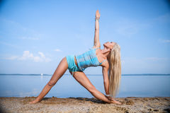 Blondes langhaariges Mädchen in einer blauen Klage ist, tuend im Sonnenlicht ausdehnend und Yoga auf einem reizenden Strand des a Stockfoto