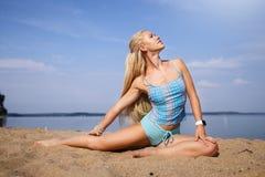 Blondes langhaariges Mädchen in einer blauen Klage ist, tuend im Sonnenlicht ausdehnend und Yoga auf einem reizenden Strand des a Lizenzfreies Stockbild