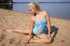 Blondes langhaariges Mädchen in einer blauen Klage ist, tuend im Sonnenlicht ausdehnend und Yoga auf einem reizenden Strand des a Stockfotografie