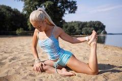 Blondes langhaariges Mädchen in einer blauen Klage ist, tuend im Sonnenlicht ausdehnend und Yoga auf einem reizenden Strand des a Stockfotos
