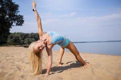 Blondes langhaariges Mädchen in einer blauen Klage ist, tuend im Sonnenlicht ausdehnend und Yoga auf einem reizenden Strand des a Lizenzfreie Stockfotos