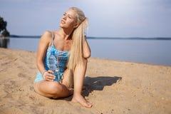 Blondes langhaariges Mädchen in einer blauen Klage ist, tuend im Sonnenlicht ausdehnend und Yoga auf einem reizenden Strand des a Lizenzfreie Stockfotografie