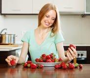 Blondes langhaariges Mädchen mit Erdbeere Stockfoto