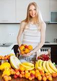 Blondes langhaariges Mädchen mit Haufen von verschiedenen Früchten Lizenzfreies Stockfoto