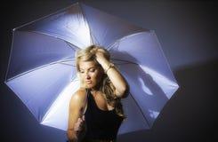 Blondes Latina-Mädchen, das Regenschirm stilisiert hält Stockfotos