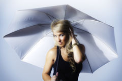 Blondes Latina-Mädchen, das Regenschirm-stilisiertes Silber hält Lizenzfreies Stockfoto