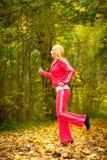 Blondes laufendes Rütteln der jungen Frau des Mädchens im Herbst  Lizenzfreies Stockfoto