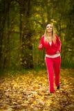 Blondes laufendes Rütteln der jungen Frau des Mädchens im Herbstfall Forest Park Lizenzfreies Stockfoto