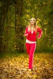 Blondes laufendes Rütteln der jungen Frau des Mädchens im Herbstfall Forest Park Lizenzfreie Stockbilder