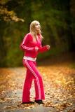 Blondes laufendes Rütteln der jungen Frau des Mädchens im Herbstfall Forest Park Stockfoto