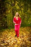 Blondes laufendes Rütteln der jungen Frau des Mädchens im Herbstfall Forest Park Stockfotos