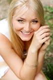 Blondes lächelndes Mädchen im Park Stockfoto