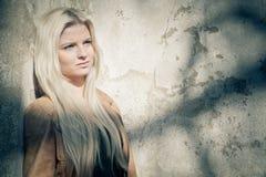 Blondes Lehnen auf grungy Wand lizenzfreie stockfotos