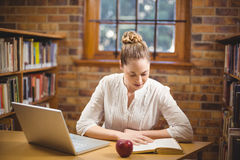 Blondes Lehrerlesebuch in der Bibliothek Lizenzfreie Stockfotos