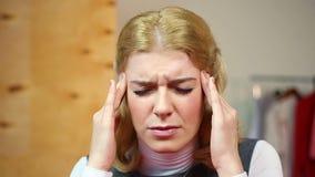 Blondes Leiden von den Kopfschmerzen Schöne Hausfrau, welche die starken Schmerz hat gesundheit stock footage
