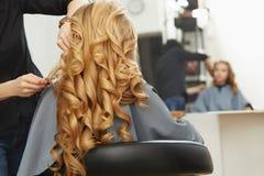 Blondes lockiges Haar Friseur, der Frisur für junge Frau I tut Stockfotografie