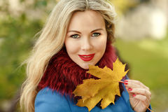 Blondes Luxusmädchen mit dem schönen Haar in einem Mantel, der einen Ahorn hält Lizenzfreies Stockbild