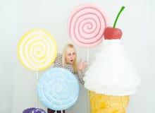 Blondes Mädchen, das auf verziertem Hintergrund mit großen Spielzeuglutschern und Eiscreme aufwirft lizenzfreies stockbild