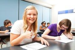 Blondes Mädchen Aces Prüfung in der Schule Lizenzfreie Stockfotos