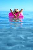Blondes Mädchen auf aufblasbarem Floß Stockbild