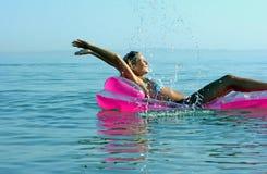 Blondes Mädchen auf aufblasbarem Floß Lizenzfreie Stockfotos