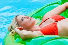 Blondes Mädchen auf aufblasbarem im Pool stockfotos