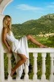 Blondes Mädchen auf dem Balkon mit Bergblick lizenzfreies stockbild