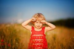 Blondes Mädchen auf dem Gebiet mit Blumen Lizenzfreie Stockfotografie