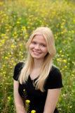 Blondes Mädchen auf dem Gebiet umgeben durch Blumen Lizenzfreies Stockfoto