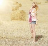Blondes Mädchen auf dem sonnigen Herbstgebiet Stockbilder