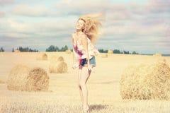 Blondes Mädchen auf dem sonnigen Herbstgebiet Stockfoto