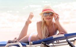 Blondes Mädchen auf dem Strand mit Sommerhut und -Sonnenbrille Stockbilder