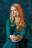 Blondes Mädchen auf einem grünen Hintergrund in einem Kleid des langen Grüns Stockfotos