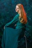 Blondes Mädchen auf einem grünen Hintergrund in einem Kleid des langen Grüns Lizenzfreie Stockbilder