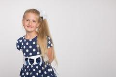 Blondes Mädchen auf einem grauen Hintergrund Lizenzfreies Stockbild