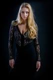 Blondes Mädchen auf einem schwarzen Hintergrund in einem dunklen Guipurespitzenkleid Lizenzfreie Stockfotografie
