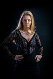 Blondes Mädchen auf einem schwarzen Hintergrund in einem dunklen Guipurespitzenkleid Lizenzfreie Stockfotos