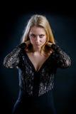 Blondes Mädchen auf einem schwarzen Hintergrund in einem dunklen Guipurespitzenkleid Lizenzfreie Stockbilder