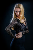 Blondes Mädchen auf einem schwarzen Hintergrund in einem dunklen Guipurespitzenkleid Stockfoto
