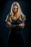 Blondes Mädchen auf einem schwarzen Hintergrund im dunklen Guipurespitzenkleid Lizenzfreie Stockfotos