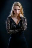 Blondes Mädchen auf einem schwarzen Hintergrund im dunklen Guipurespitzenkleid Lizenzfreies Stockfoto