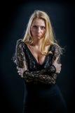 Blondes Mädchen auf einem schwarzen Hintergrund im dunklen Guipurespitzenkleid Stockbilder