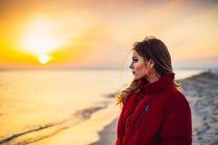 Blondes Mädchen auf Hintergrund des Meeres und des Sonnenuntergangs Stockfotos