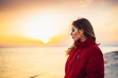 Blondes Mädchen auf Hintergrund des Meeres und des Sonnenuntergangs Lizenzfreies Stockbild