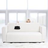 Blondes Mädchen auf Sofa Stockfoto