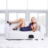 Blondes Mädchen auf Sofa Stockbilder