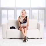 Blondes Mädchen auf Sofa Stockfotos