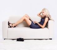 Blondes Mädchen auf Sofa Lizenzfreie Stockfotos