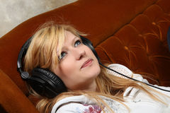 Blondes Mädchen auf Sofa hörend Musik mit Kopfhörern Stockbild
